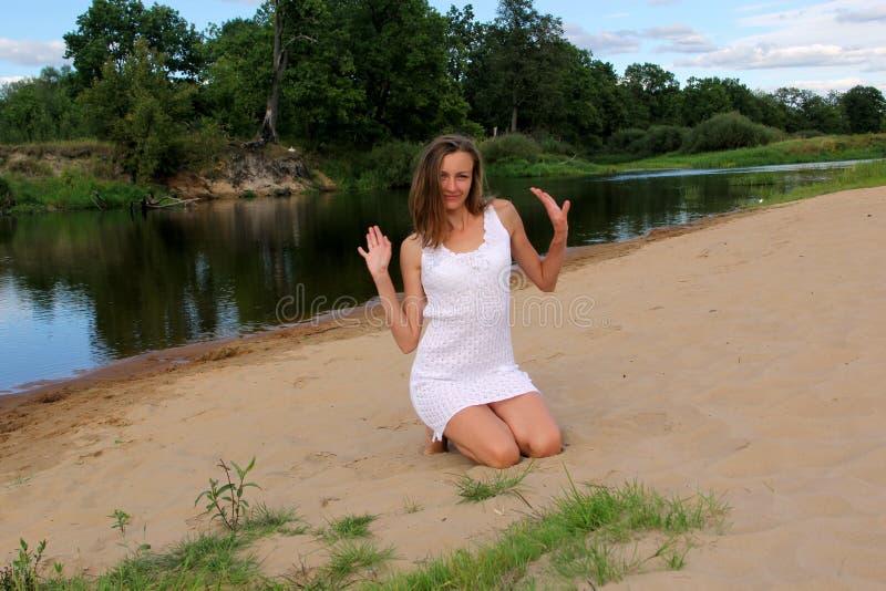 Flicka som sitter på hennes knä i sanden på flodbanken fotografering för bildbyråer