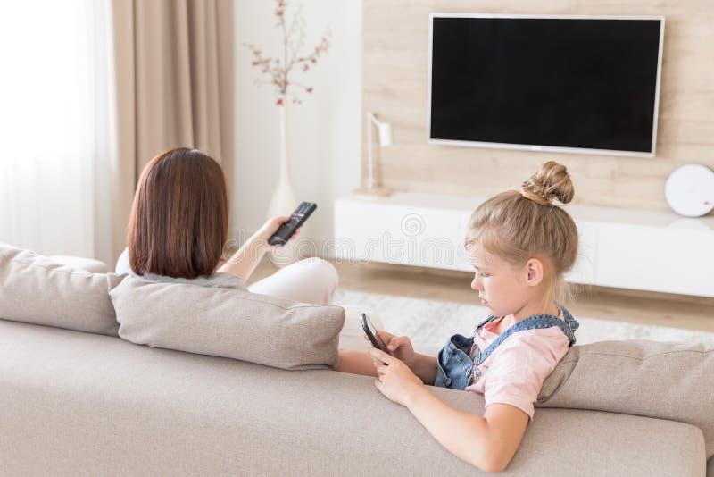 Flicka som sitter på soffan och håller ögonen på något intressera i mobiltelefon medan hållande ögonen på tv för moder royaltyfri foto