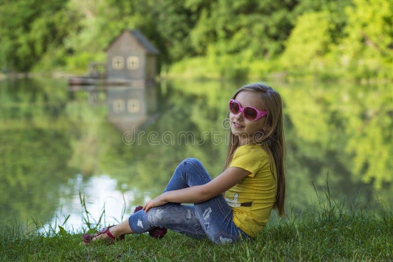 Flicka som sitter utanför på en solig dag Liten flicka som sitter i sommarskogen royaltyfri bild