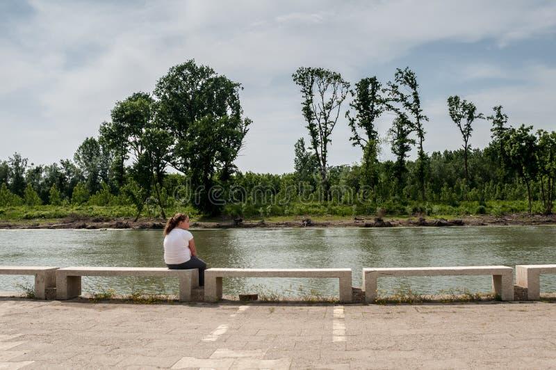 flicka som sitter vid floden royaltyfri bild