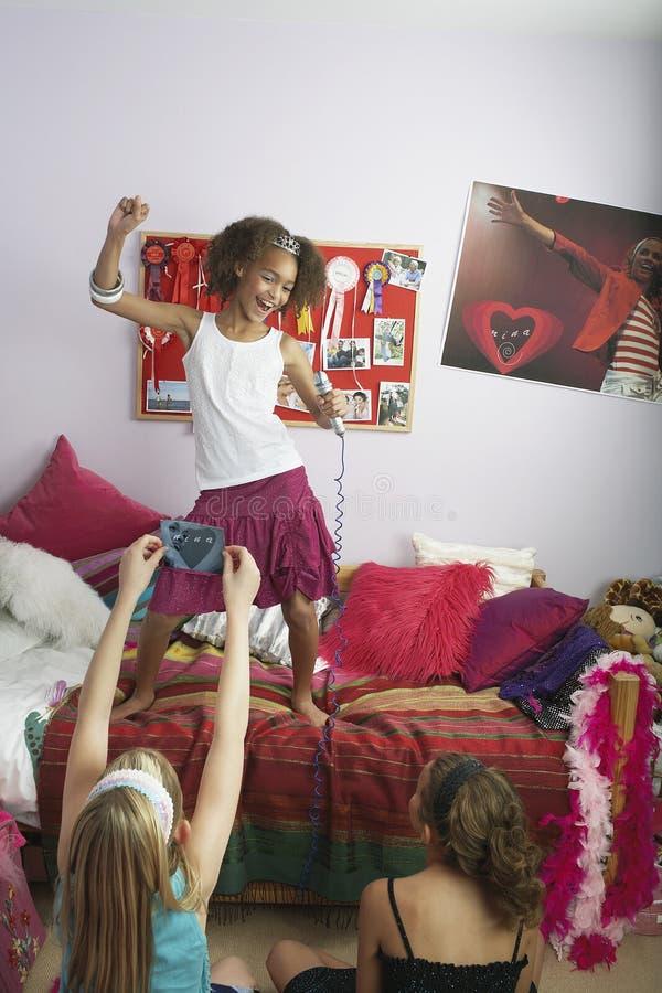 Flicka som sjunger i Front Of Friends arkivbild