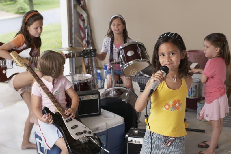 Flicka som sjunger in i mikrofonen med vänner som spelar musikinstrumentet royaltyfri bild