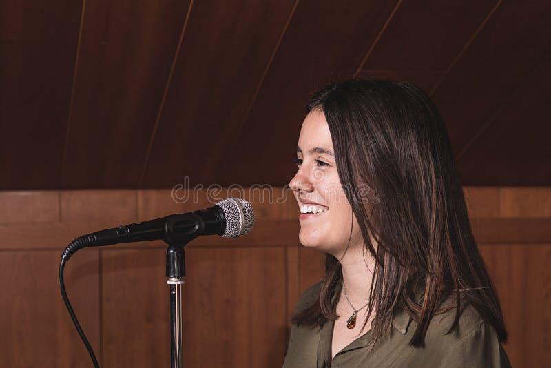 Flicka som sjunger med en mikrofon i en musikstudio arkivbilder
