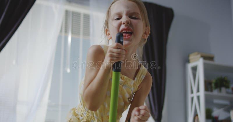 Flicka som sjunger med kvasthandtaget arkivfoto