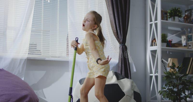 Flicka som sjunger med kvasthandtaget royaltyfri foto