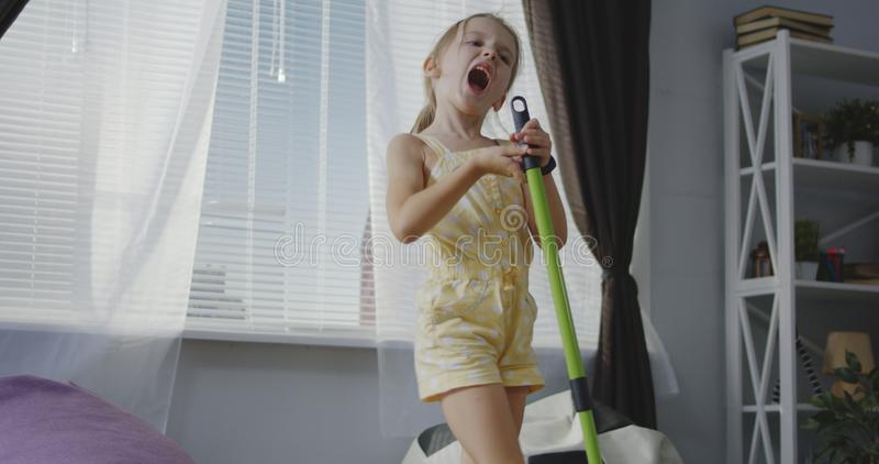 Flicka som sjunger med kvasthandtaget arkivfoton