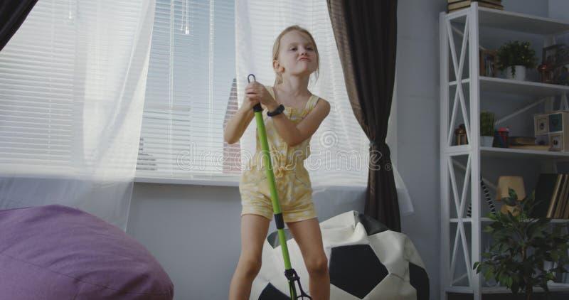 Flicka som sjunger med kvasthandtaget arkivbild