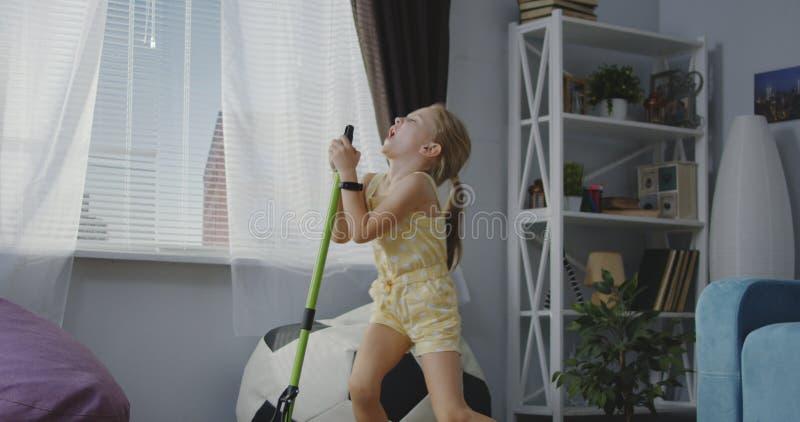 Flicka som sjunger med kvasthandtaget royaltyfria foton