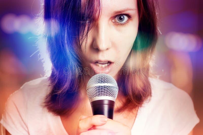 Flicka som sjunger med mikrofonen i hennes hand på en etapp arkivfoto