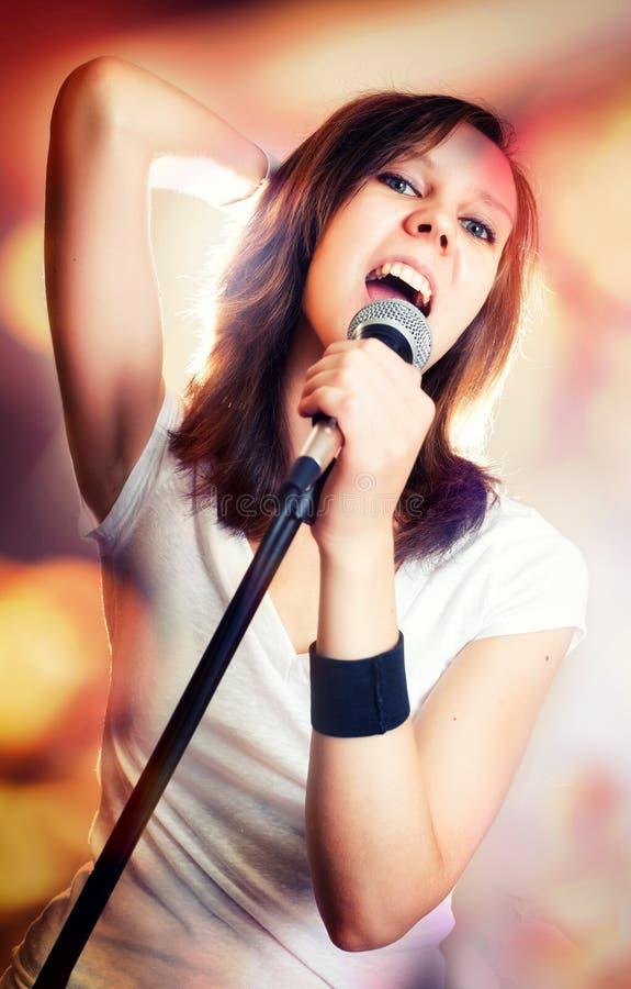 Flicka som sjunger med mikrofonen i hennes hand på en etapp royaltyfria foton