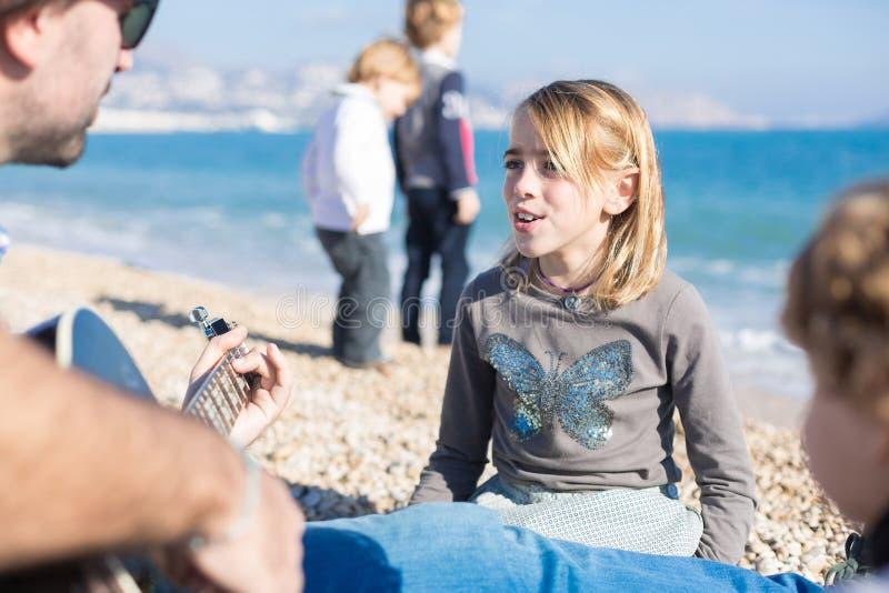 Flicka som sjunger medan man som spelar gitarren på stranden arkivbild