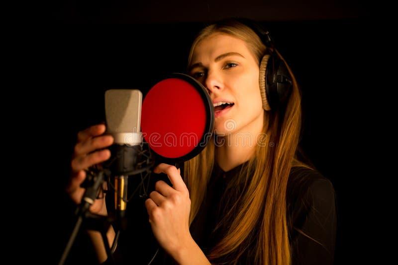 Flicka som sjunger till mikrofonen i studio Process av att skapa ny sång arkivbilder