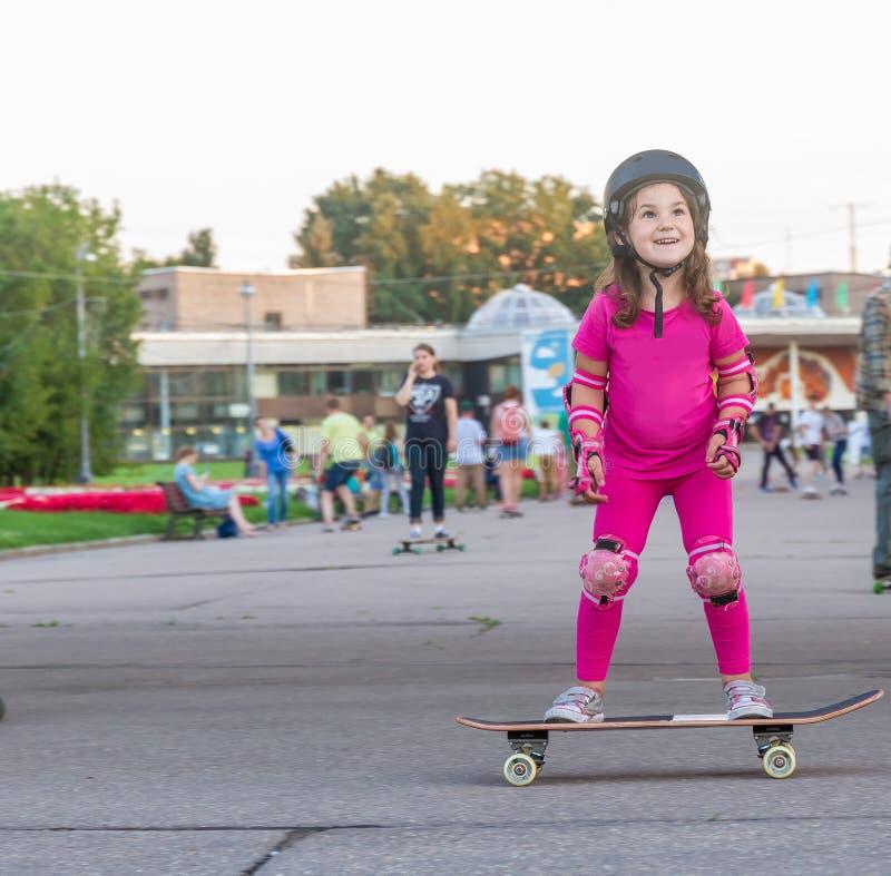 Flicka som skateboarding på naturlig bakgrund arkivfoto