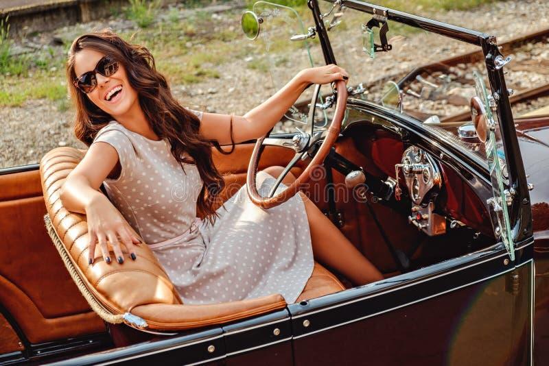 Flicka som skrattar, medan köra den gamla klassiska bilen royaltyfri bild