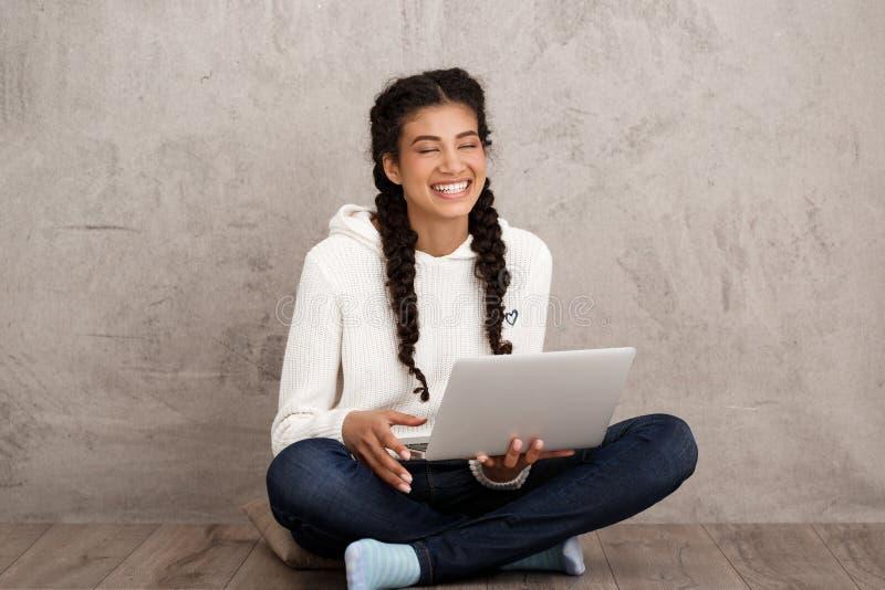 Flicka som skrattar och att rymma bärbara datorn som sitter på golv över beige bakgrund arkivbild