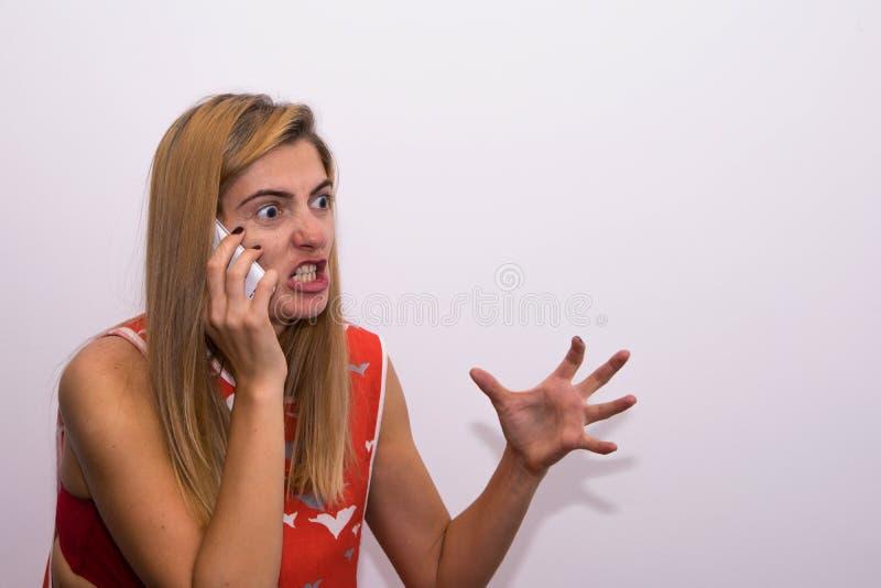 Flicka som skriker på telefonen arkivfoto