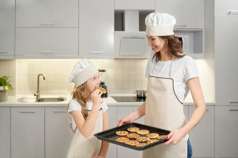 Flicka som smakar hemlagade amerikanska kakor som lagas mat av modern arkivfoto