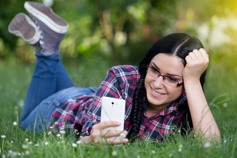 Flicka som smsar på den smarta telefonen på gräs fotografering för bildbyråer