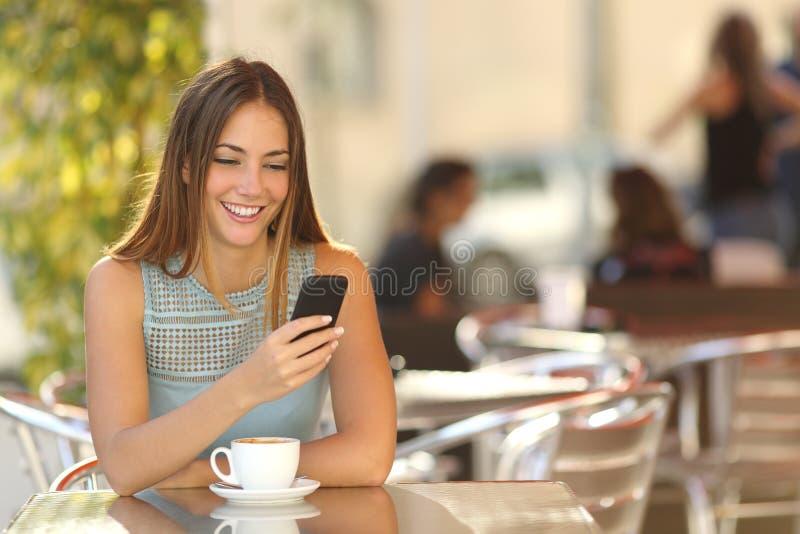 Flicka som smsar på telefonen i en restaurang royaltyfri bild