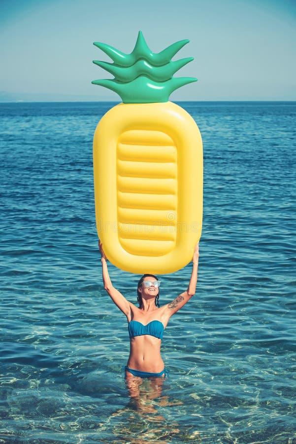 Flicka som solbadar på stranden med luftmadrassen Sexig kvinna på det karibiska havet i Bahamas Uppblåsbar madrass för ananas arkivfoto