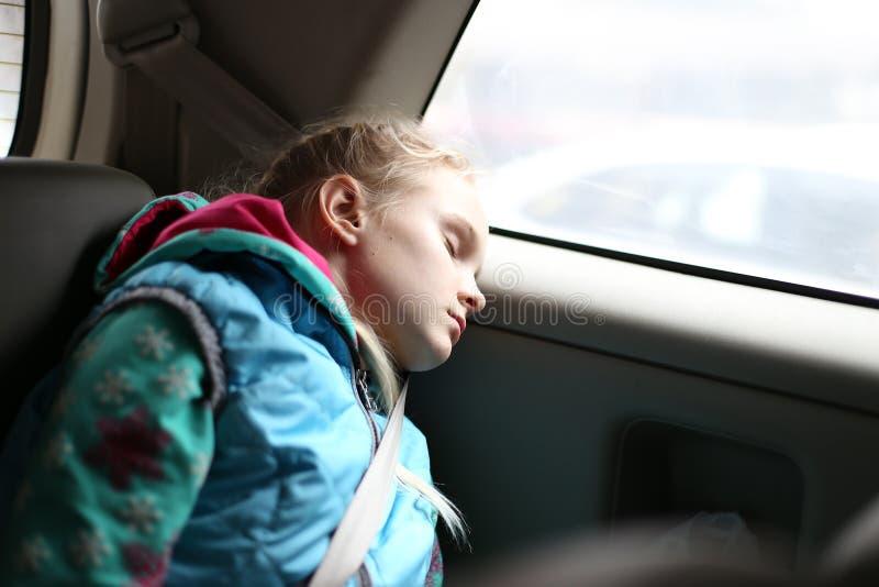 Flicka som sover i bil royaltyfri bild