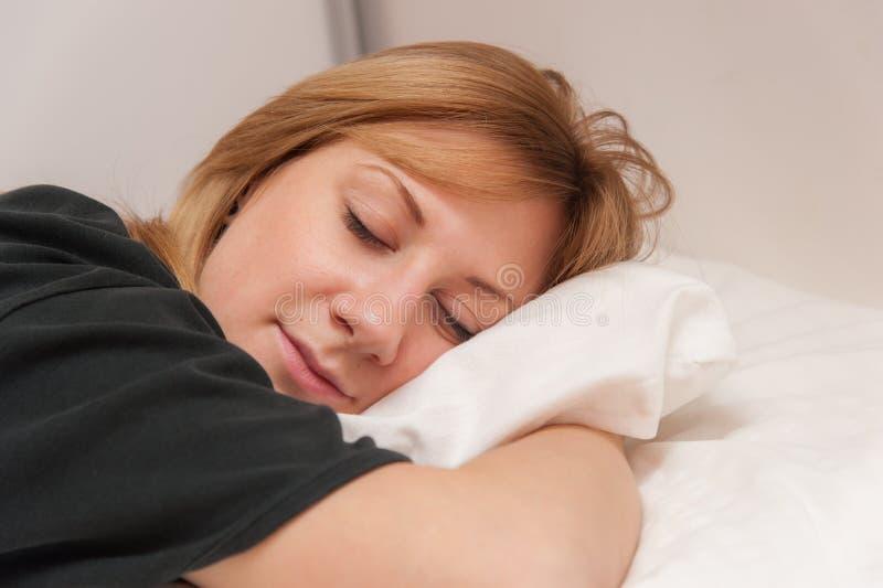 Flicka som sover i säng arkivbilder