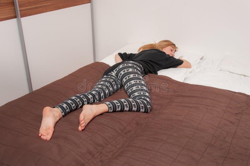 Flicka som sover i säng arkivbild