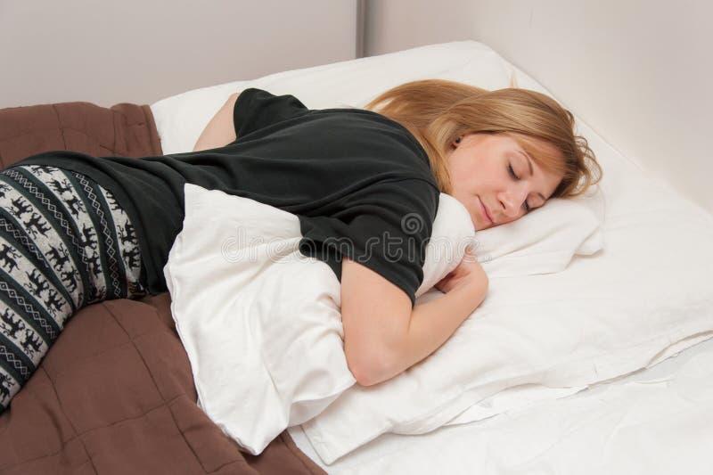 Flicka som sover i säng royaltyfri bild