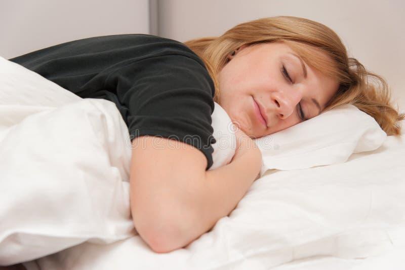 Flicka som sover i säng royaltyfri foto