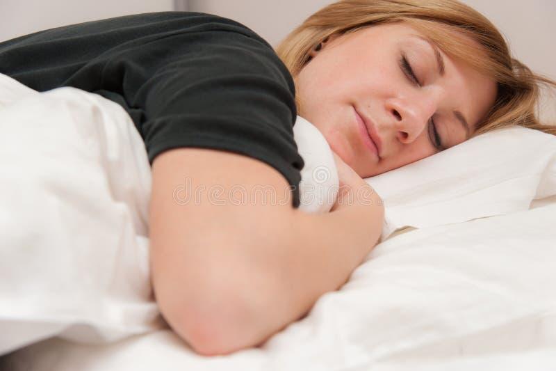 Flicka som sover i säng royaltyfria foton