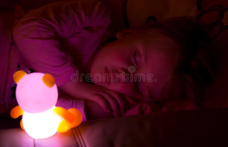 Flicka som sover med den ljusa leksaken fotografering för bildbyråer