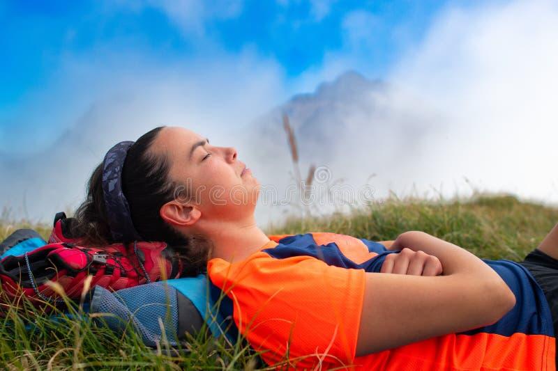 Flicka som sover med hennes huvud på ryggsäcken i en bergäng fotografering för bildbyråer