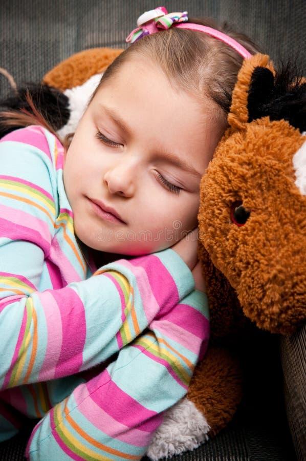 Flicka som sover med nallebjörnen arkivfoton