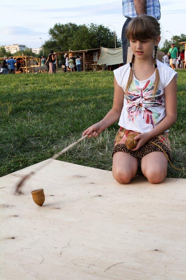 Flicka som spelar den gasing ` för ` eller överkantsnurret, ett traditionellt gammalt för ryss royaltyfri bild