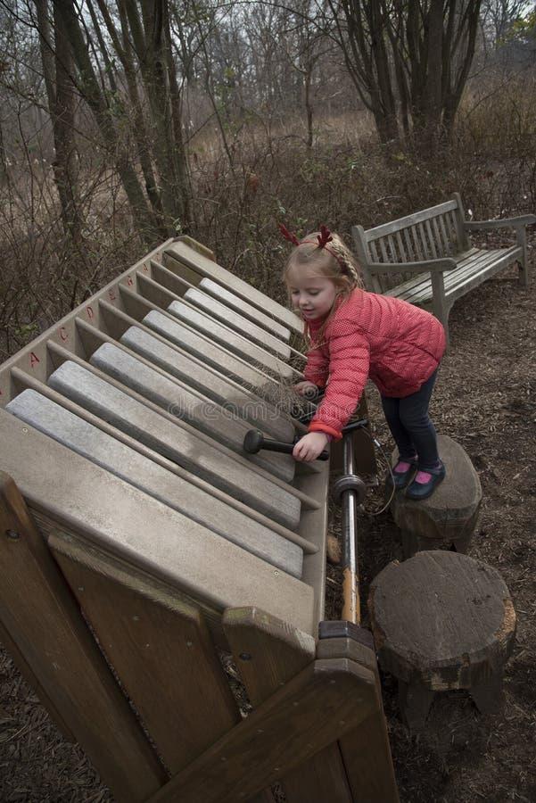 Flicka som spelar en xylofon i en trädgård royaltyfria bilder