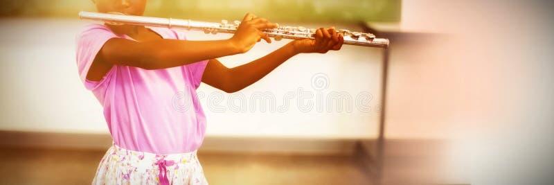 flicka som spelar flöjten i klassrumet royaltyfri foto