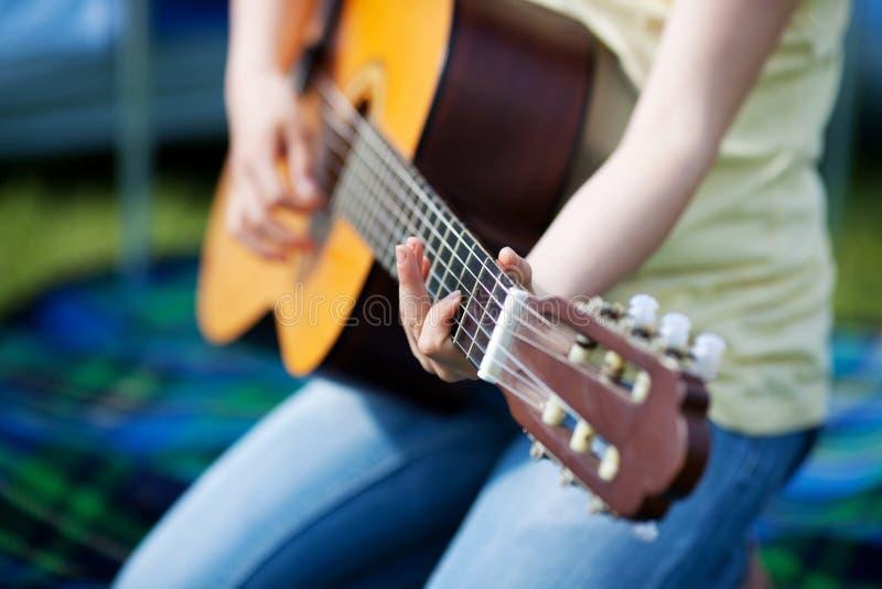 Flicka som spelar gitarren arkivfoto