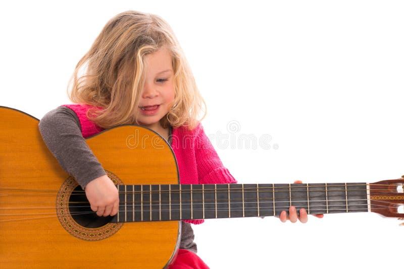 Flicka som spelar gitarren arkivbild