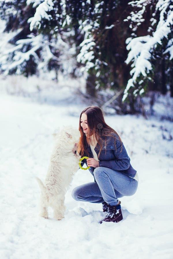 Flicka som spelar hennes hund i vinter i skogen arkivbild