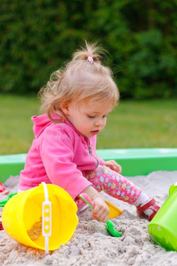 Flicka som spelar i en sandask arkivbilder