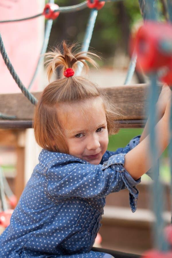 Flicka som spelar i lekplatsområde royaltyfri foto