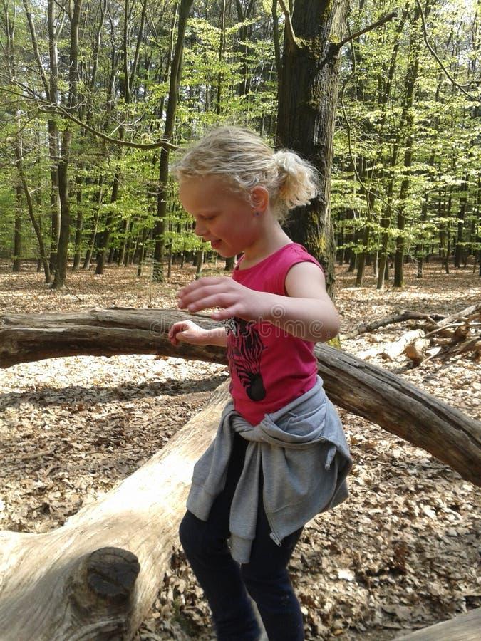Flicka som spelar i skogen arkivfoto