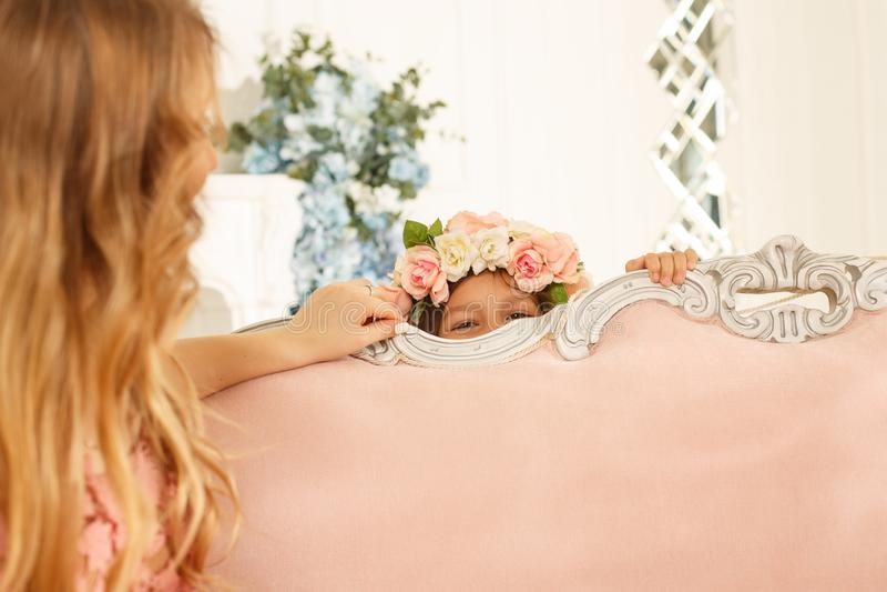 Flicka som spelar kurragömma med hennes moder fotografering för bildbyråer