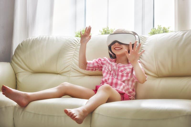 Flicka som spelar leken i virtuell verklighetexponeringsglas fotografering för bildbyråer
