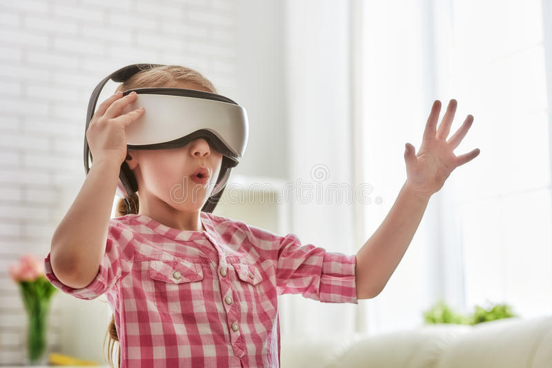 Flicka som spelar leken i virtuell verklighetexponeringsglas arkivbilder