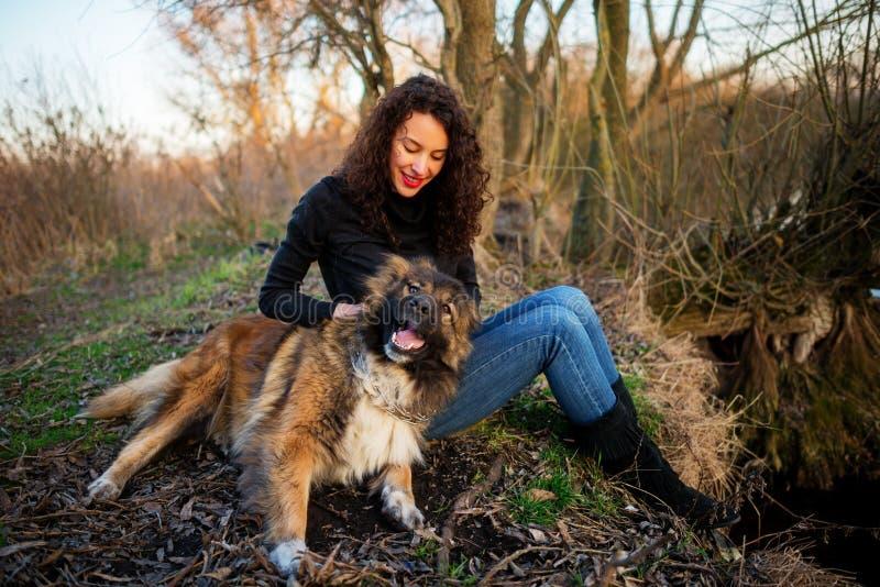 Flicka som spelar med den Caucasian herdehunden, höst royaltyfri foto