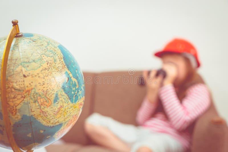 Flicka som spelar med det binokulär och översiktsjordklotet för det conc loppet royaltyfria bilder