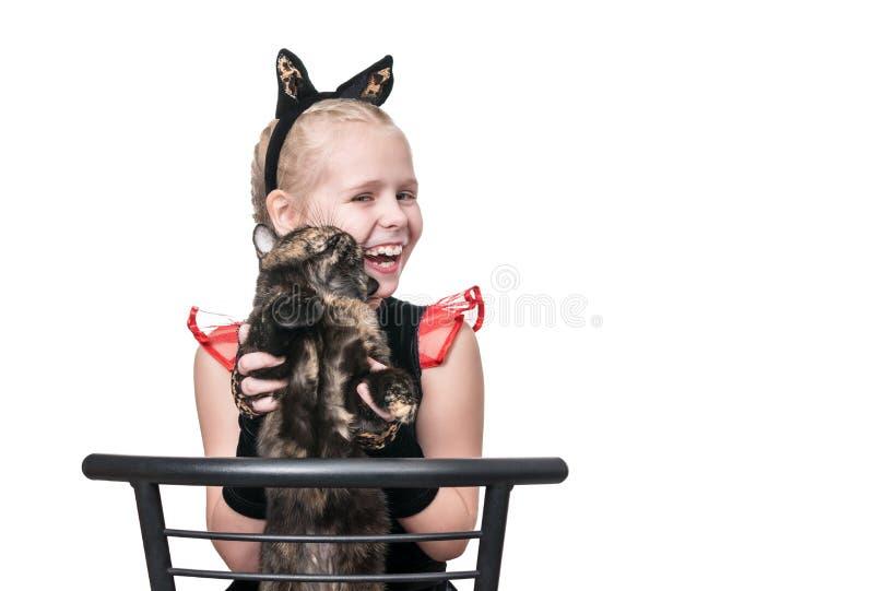 Flicka som spelar med en katt arkivfoton