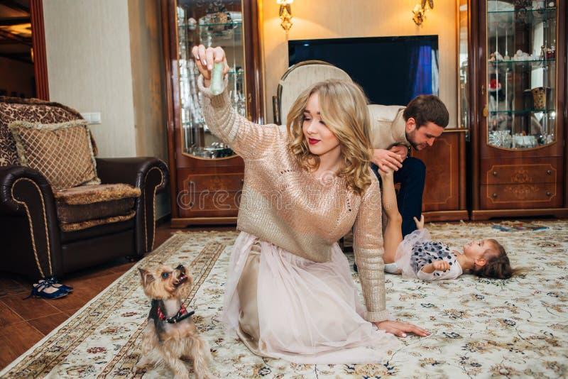 Flicka som spelar med ett sammanträde för hundhus på golvet royaltyfri bild
