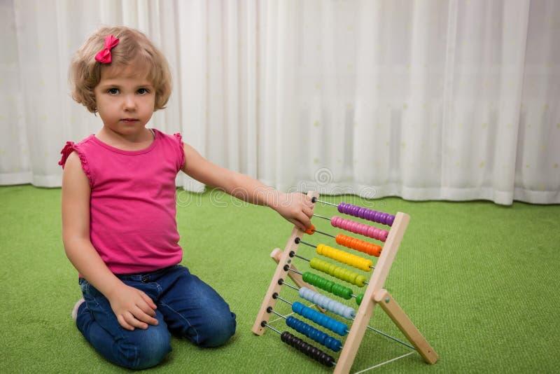 Flicka som spelar med färgställningar royaltyfria foton